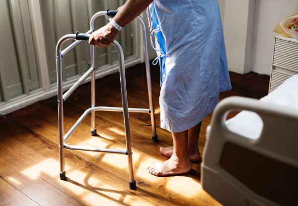 person in hospital gown using walking frame beside hospital bed